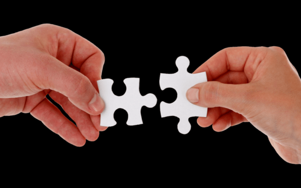Two hands each holding a puzzle piece inches away from connecting them