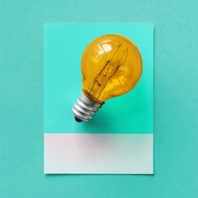 Yellow light bulb placed on an aqua colour swatch