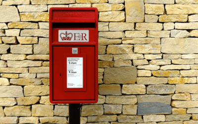 Red post box against a sandy coloured stone wall