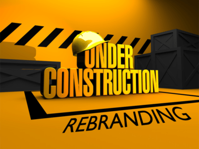 Yellow background with large text spelling out 'Under Construction' with hard hat on top. Black construction signage printed on the floor with word 'rebranding'